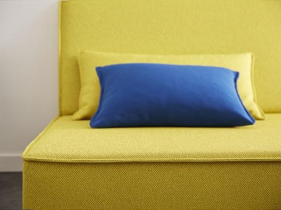 Sofà giallo con il cuscino blu