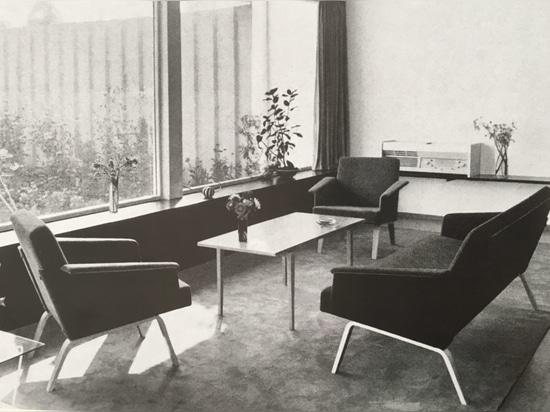 Nel 1957, Herbert Hirche ha progettato l'estesa gamma di 480 mobili imbottiti con le strutture di legno solide lineari e molto delicate (fondo). Come variante, le 486 sedie di salotto hanno avute p...
