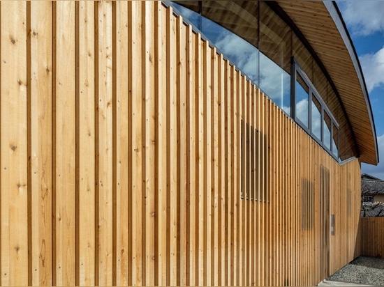 il tetto di legno curvo della grata appende sopra la scuola materna del cielo blu dei nasca nel Giappone