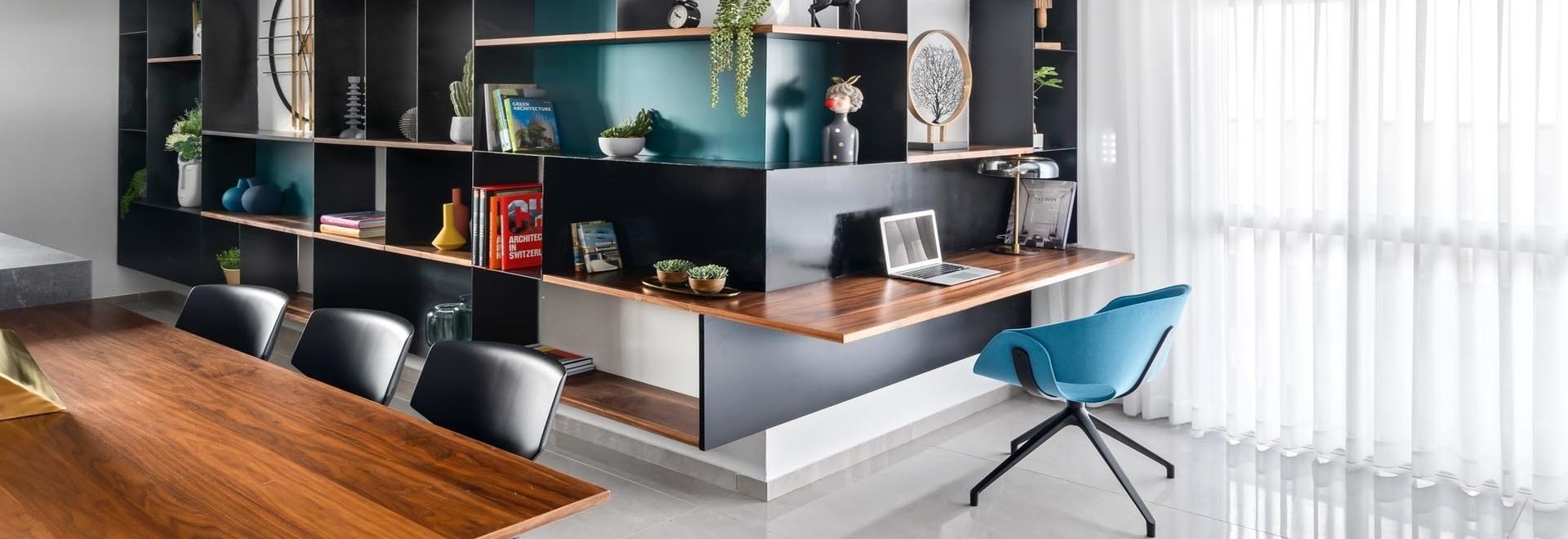 Una piccola scrivania è stata inclusa in questo muro avvolgente di scaffalature progettato per mostrare pezzi decorativi
