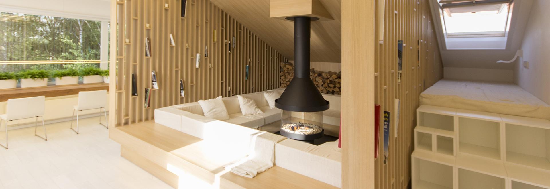 Un salotto confortevole con scaffalature aperte circonda un camino in questa casa