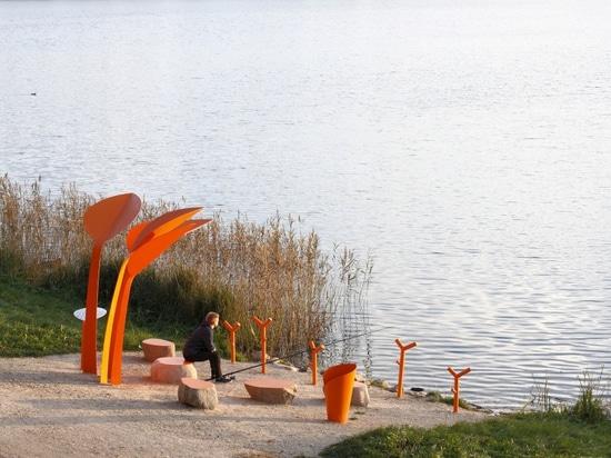 Questo posto a sedere pubblico accanto a un lago in Lettonia fornisce un luogo di riposo una canna da pesca