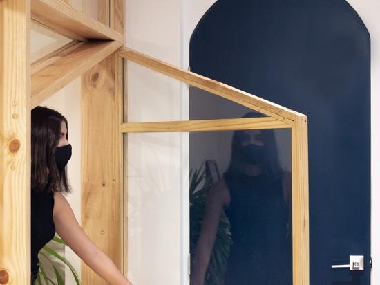 La scaffalatura di pino e vetro racchiude l'ufficio in Ecuador