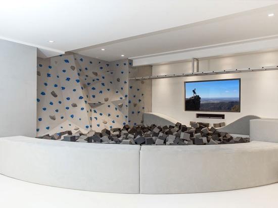 Gli angoli per sedersi sono stati costruiti in un muro di scaffalature in questa stanza dei giochi per bambini