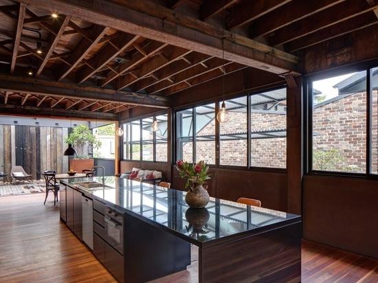Piastrelle nere smaltate presentano un esterno sofisticato per questa casa che era un magazzino