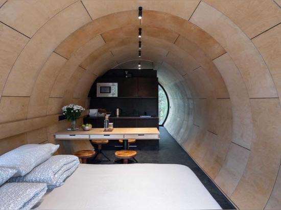 Questa cabina a forma di tubo con un esterno in metallo lucido si libra sul paesaggio circostante