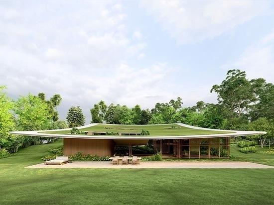 Un monumentale piano del tetto racchiude i volumi raggruppati della casa taperá del Brasile